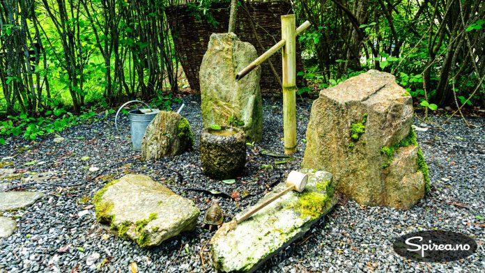 I denne mørke delen av hagen er det blitt plass til et vannelement mellom noen dekorative steiner.