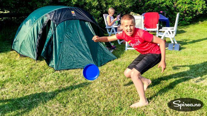 """Vi overnattet i telt og storkoste oss. Her leker Andreas med en frisbee, mens Bjørnhild slapper av i plast-møblement vi """"tjuvlånte"""" fra en campinghytte i nærheten."""