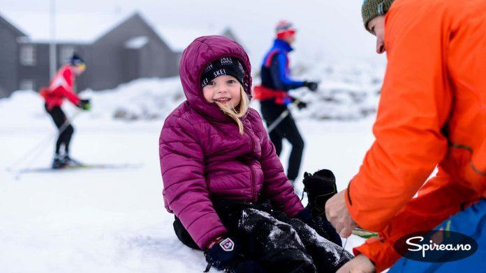 Fem år gamle Astrid venter spent på at far snører på skøytene, mens skiløpere skøyter forbi i bakgrunnen.