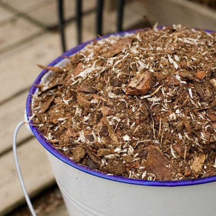 Hver gang du fyller matavfall i komposten, må du også fylle på litt strø. Vi bruker et kompoststrø bestående av spon og bark som suger til seg fuktighet. Foto: Hasselfors Garden