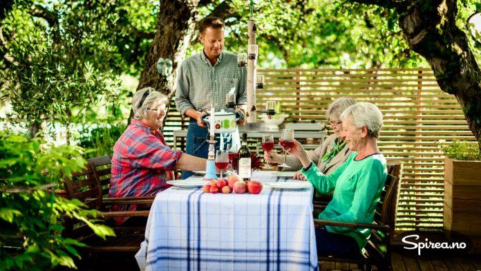 På sitteplassen under epletrærne kan Øystein invitere gjester til bords.