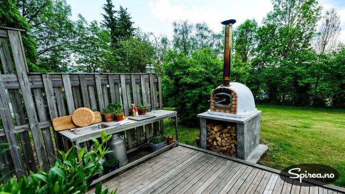 Steinovnsmodellen Barboletta koster 8500 kroner, og har et design som gjør at den passer langt bedre inn i et hagemiljø enn en gassgrill. Utekjøkkenet til venstre har Rasmus og Lina laget selv av betong og stål.