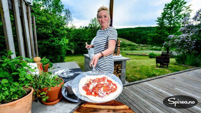Etter at alt fyllet er lagt på, legger du pizzaen over på en pizzaspade. Husk å bruke litt mel under så deigen ikke setter seg fast i spaden.