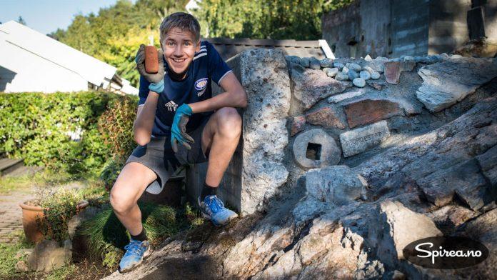 Henrik viser fram en liten murstein som vi har tatt vare på i mange år. Den ble funnet på en strand i Danmark i 2008. Nå ligger den i hullet på en slipstein vi murte inn.