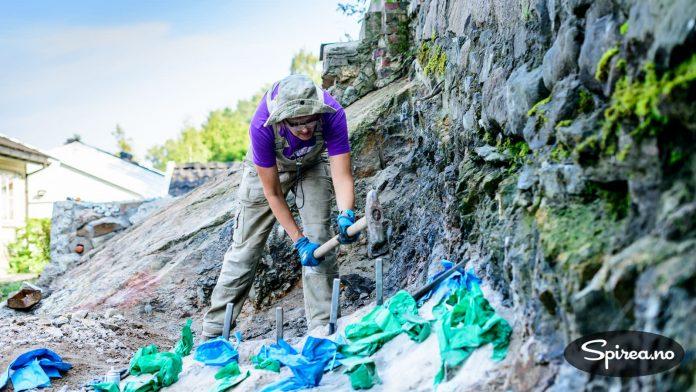 """Bjørnhild er ikke spesielt treffsikker med slegga, og foretrekker derfor Trollkraft til """"selvsprenging"""" fremfor fjellkiler. (De grønne og blå plastposene brukes for å unngå at hullene tettes igjen etter boring.)"""
