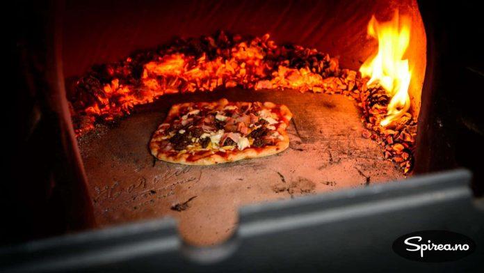 Når veden er blitt til glør, og temperaturen er minst 300 grader, kan du steke pizza.