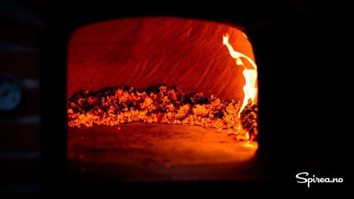 Før du kan steke pizzaene, rakes glørne inn til sidene i steinovnen.