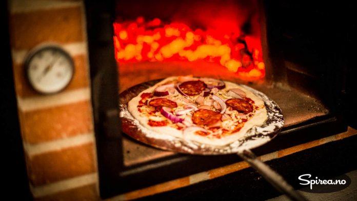 Bruk pizzaspade med langt skaft for å sette inn pizzaen, ovnen er veldig varm!